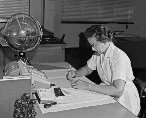 "NASA research mathematician Katherine Johnson is photographed at her desk at NASA Langley Research Center with a globe, or ""Celestial Training Device,"" in 1962."