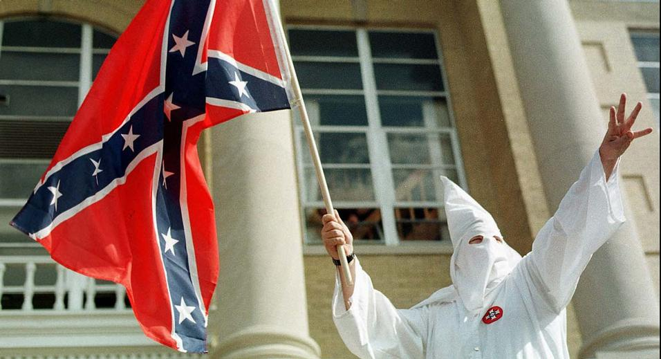 A member of the American Knights of the Ku Klux Klan waves the Confederate flag during a klan rally on the steps of the Warrick County courthouse in Boonville, Ind., on Saturday, Oct. 17, 1998.