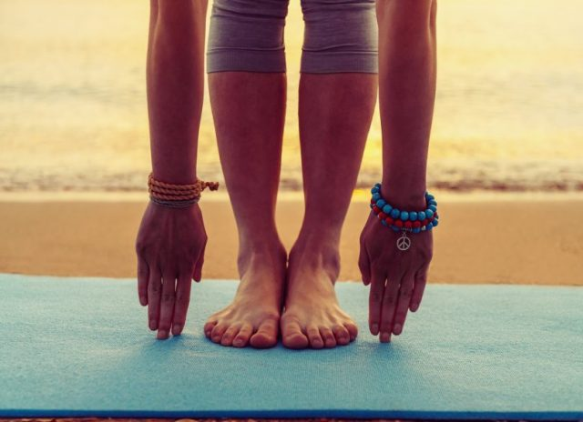 Young woman doing yoga exercise on beach near the sea at sunset in summer face is not visible
