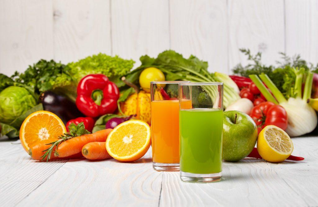 Diverso vegetais e frutas dispostos sobre uma mesa de tábua branca junto com dois copos cheios de suco, sendo um na cor amarela e outro na cor verde.