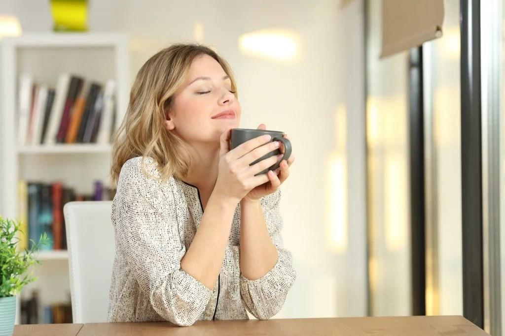 Mulher loura, com aspecto tranquilo, segundo com as duas mãos uma caneca de chá. Ela está em um ambiente clean e iluminado.