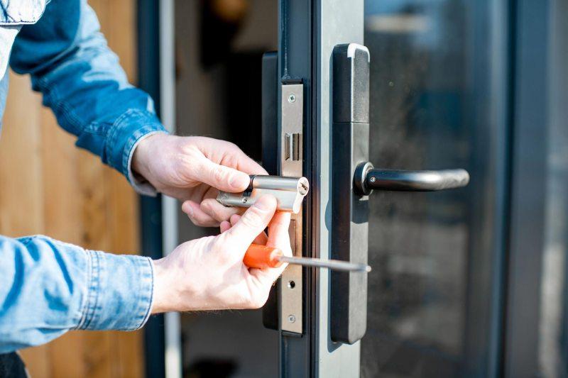 Hausmeisterservice - Ein Hausmeister repariert ein Türschloss