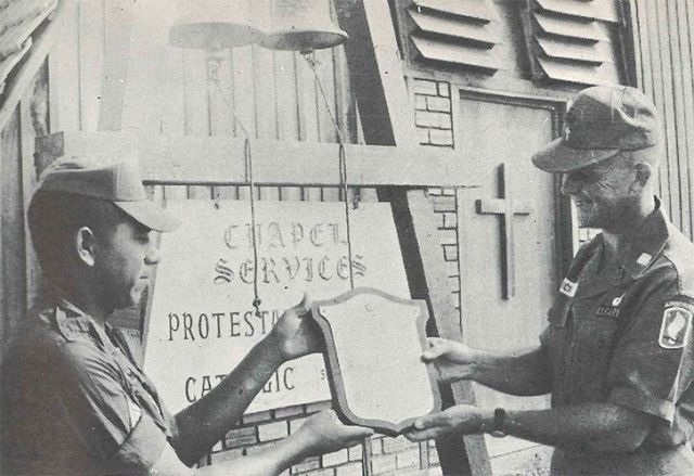 A hard-working leader, Chaplain Crick, and a young soldier examine the plaque they will place on the chapel they built in honor of their fallen comrades.