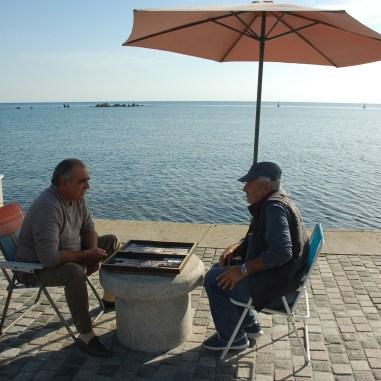 Twee mannen spelen backgammon in de haven van Paphos