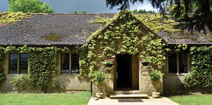Lady's Wood Shooting School Cotswold stone lodge covered in ivy