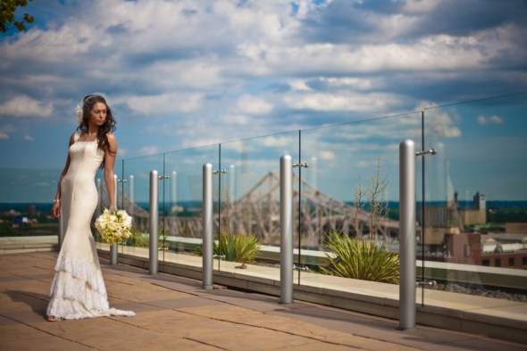 bride downtown in front of bridge and blue sky in sparkly tiered wedding dress