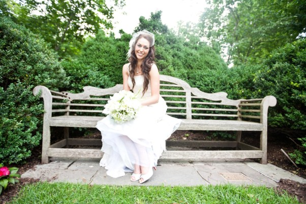 bride sitting on wooden bench in a garden with white bouquet