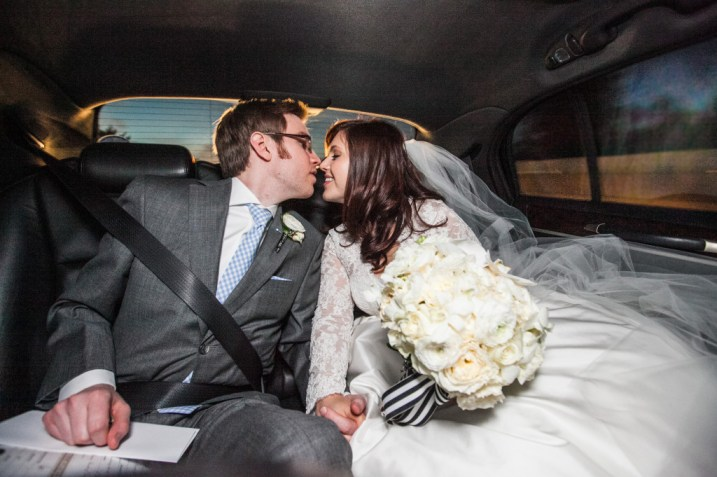 bride and groom sharing a kiss in their getaway car