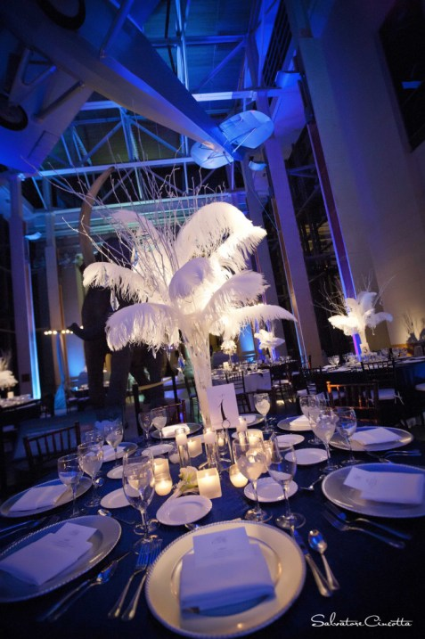 Wedding reception table with feather centerpiece and overhead airplane