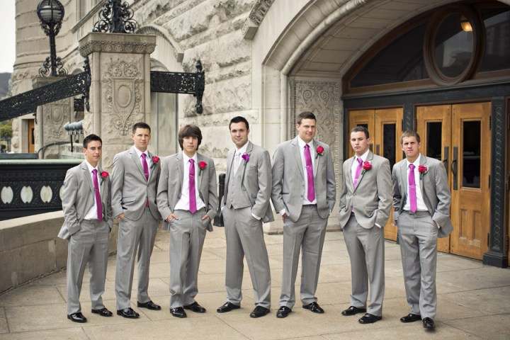 groomsmen with pink ties and boutonnieres gray suits