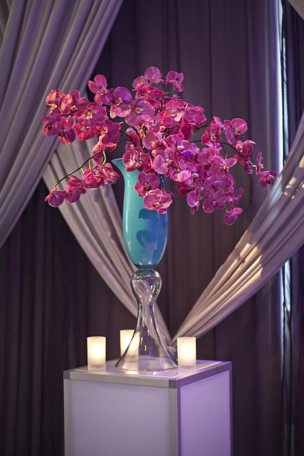 turquoise vase with purple orchids wedding aisle