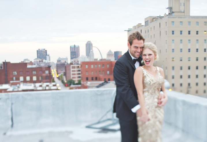 Bride and groom on rooftop with St Louis Arch in background