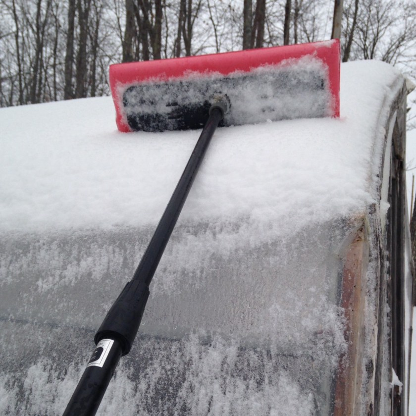 Clearing away the snow load with a foam car scraper.