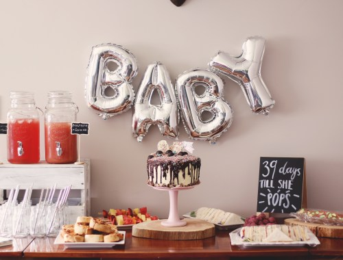 Check out this fun, boho baby shower. Foil balloons, wooden rounds and a cake to die for. plus free printable baby shower games.