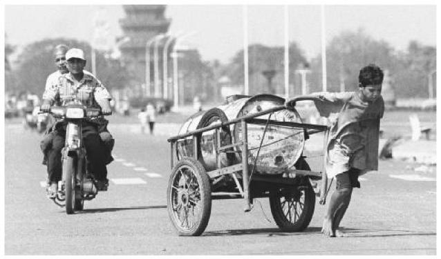 A Cambodian boy pulls a forty-four gallon drum full of water on his cart, a trip he makes eight to ten times a day.