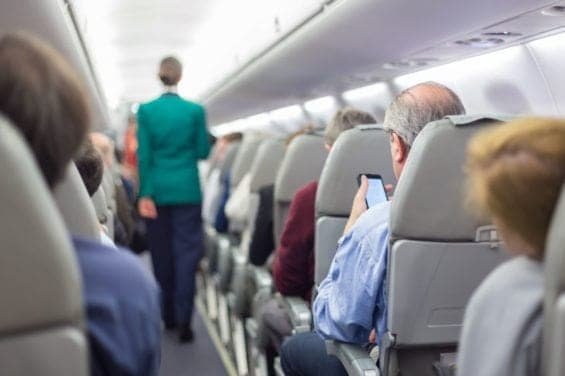 50007787 - interior of airplane with passengers on seats waiting to taik off. stewardess in green uniform walking the aisle. horizontal composition.