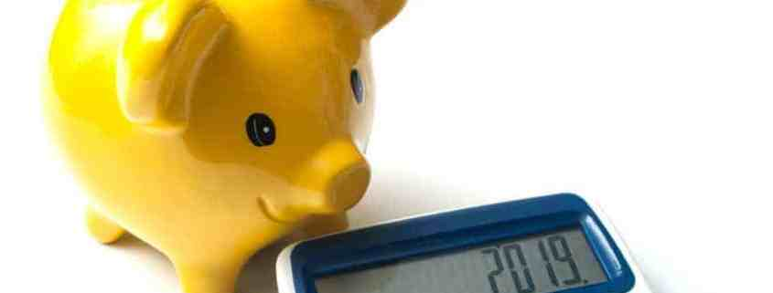 Yellow piggy bank and calculator with 2019 year on window