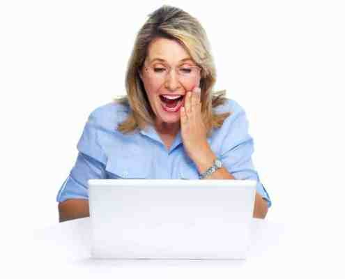 Happy senior woman with laptop experiencing best money year ever