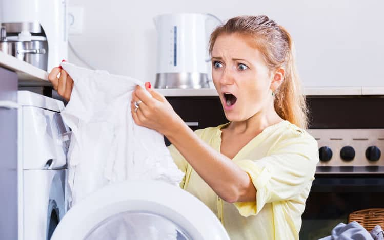 Upset girl looking at tshirt with yellow armpit stain after laundry