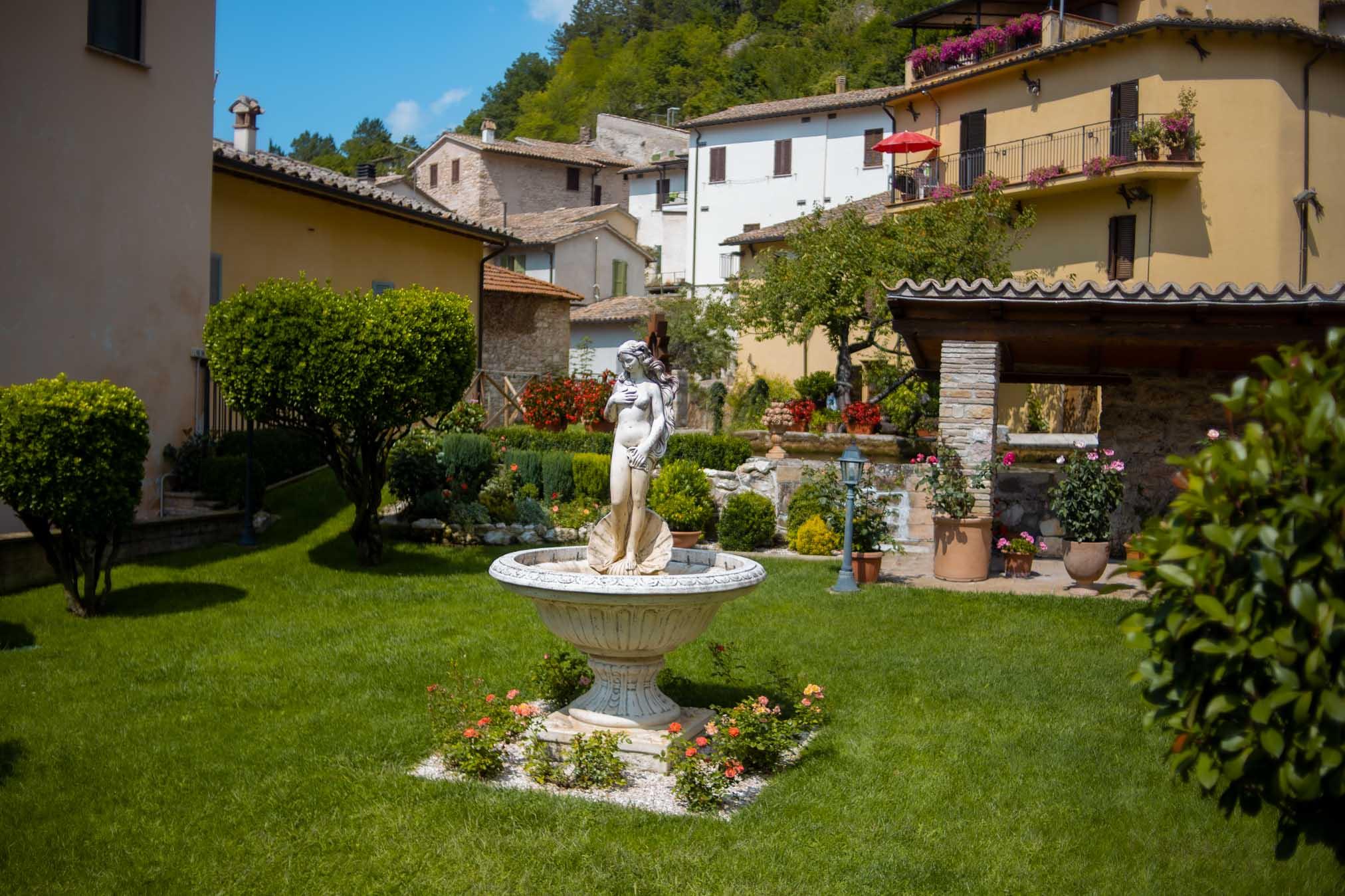 giardino curato con fiori e statua al centro di una dea a Rasiglia