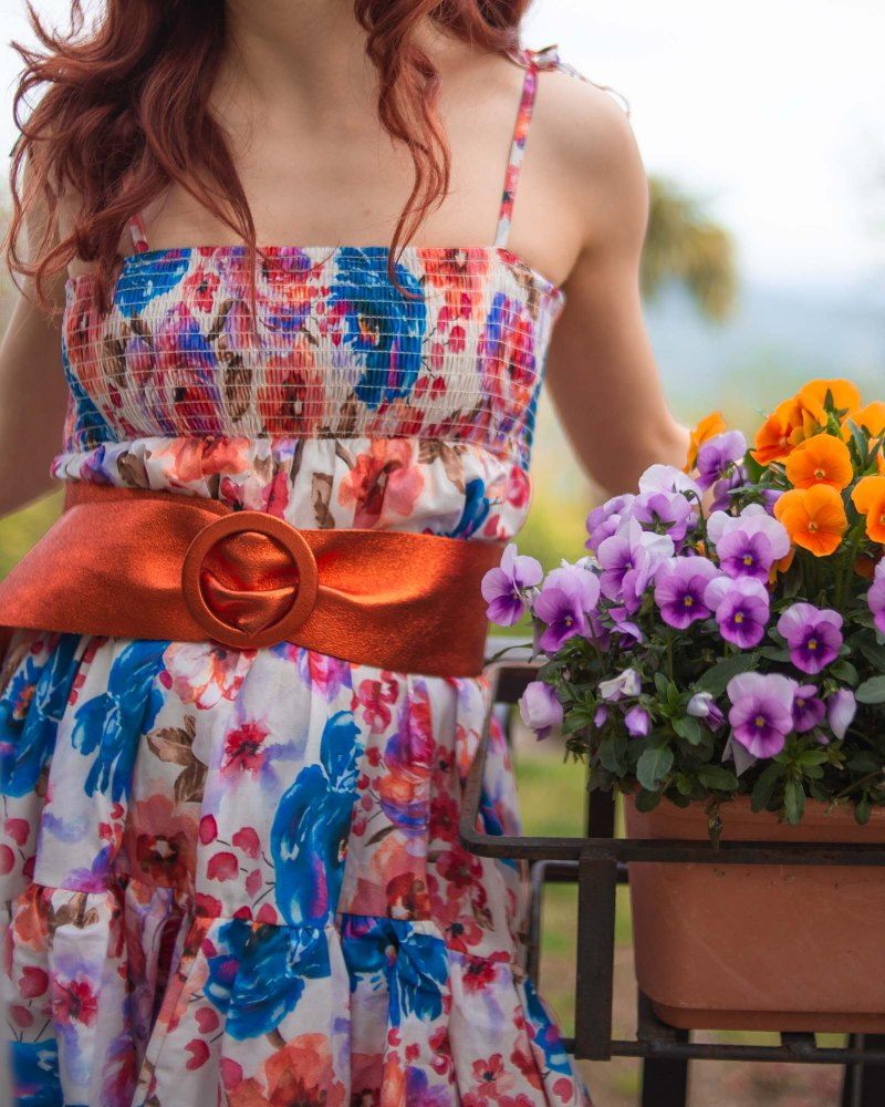 particolare su cintura metallizzata arancione su un vestito floreale estivo