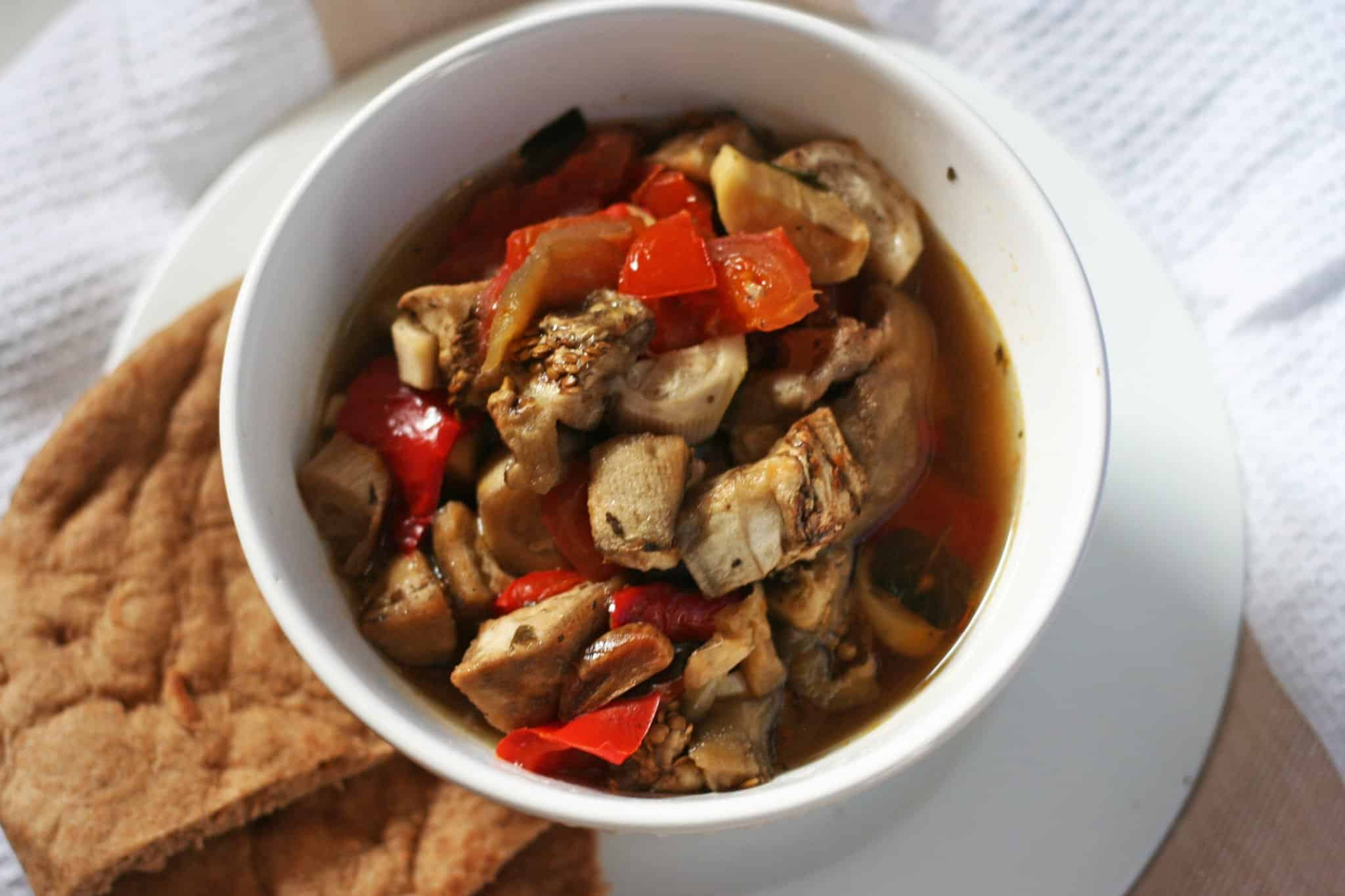 Tender eggplant and peppers slow cooked and served in a white bowl with warm pita bread in a side plate