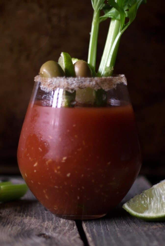 The perfect bloody mary topped with lime wedge, olives, celery in a glass rimmed with salt.