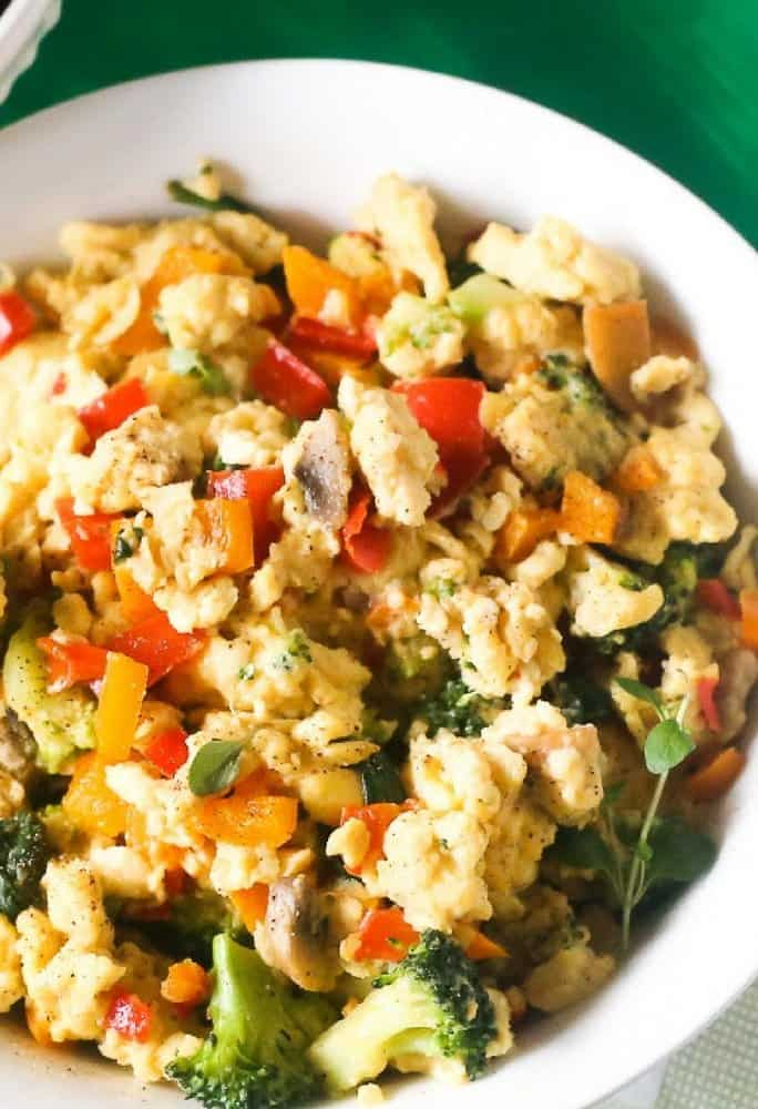 Right angle view of healthy delicious veggie egg scramble with fresh orange peppers, zucchini seasoned with fresh herbs