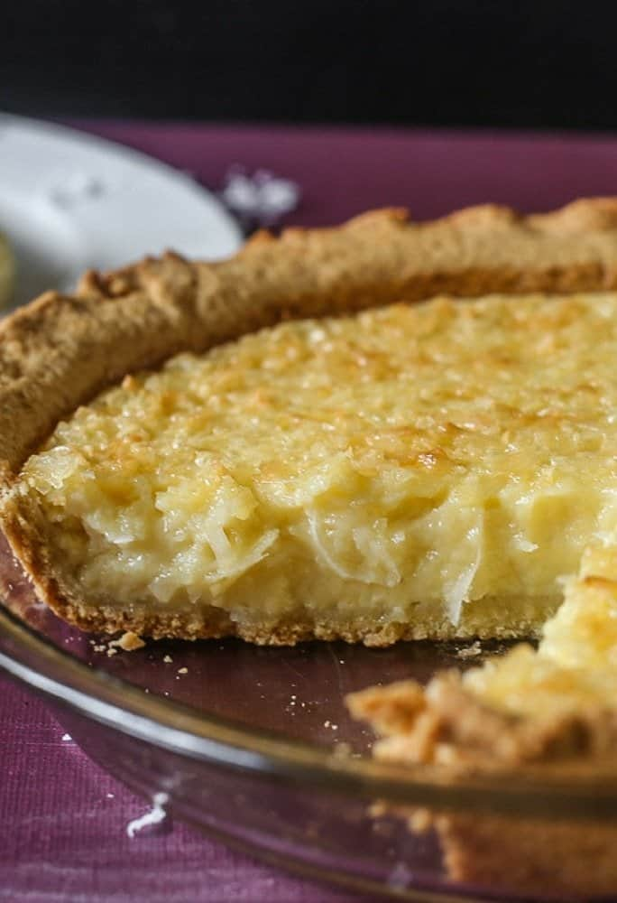 A delicious old fashioned coconut custard pie sliced to show the delicious creamy coconut cream slice