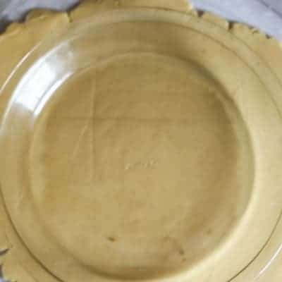 An arial view of a buttery flaky pie crust that has been rolled out and a clear pie pan is on top of the flaky pie crust to ensure the pie dough is larger than the pie pan.