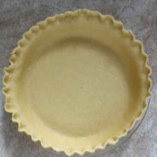 An aerial view of a buttery pie crust recipe in a clear pie pan with fluted edges that is not yet baked