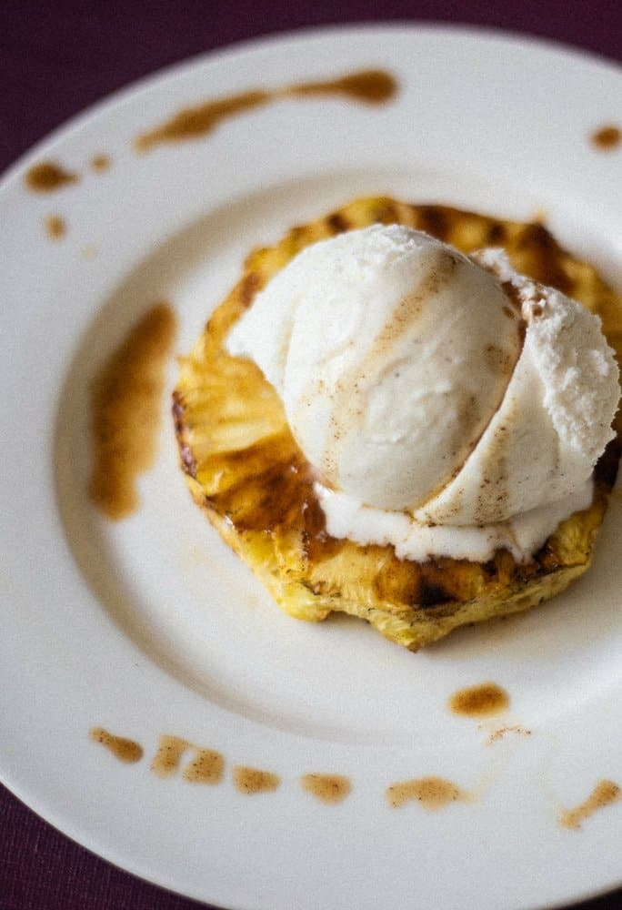 Delicious grilled pineapple marinated in a rum sauce and grilled to perfection. Topped with vanilla ice cream and drizzled with more rum sauce on a white plate.