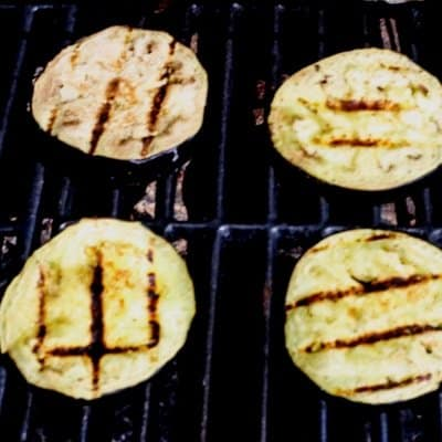 Eggplant that has been seasoned and brushed with olive oil is being grilled to make an awesome grilled eggplant recipe.
