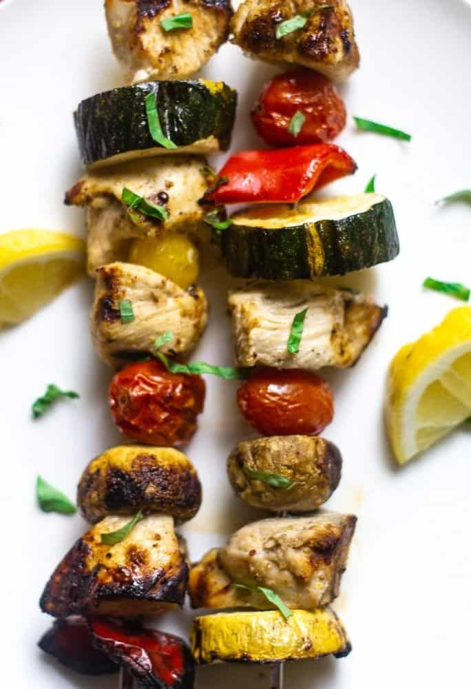 overhead view of grilled citrus marinated chicken kabobs on a metal skewer with zucchini, tomatoes, and mushrooms