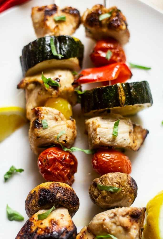 Grilled Chicken Shish Kabobs and vegetables with a citrus marinade on skewers that have been grilled on a white platter with with chopped parsley and lemon wedges