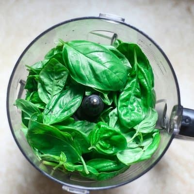 packed basil leaves in the food processor ready to make basil pesto