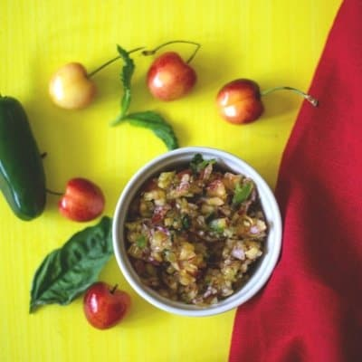Fresh cherry salsa in a white bowl , red linen to the right of the bowl. Skylar Rae®Cherries and a jalapno around the bowl of cherry salsa