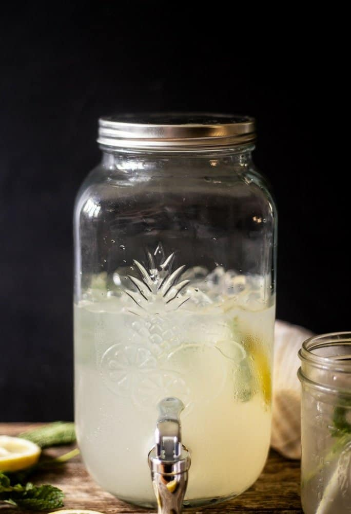 Fresh homemade mint ginger lemonade fills a large glass canister with lots of ice and mint
