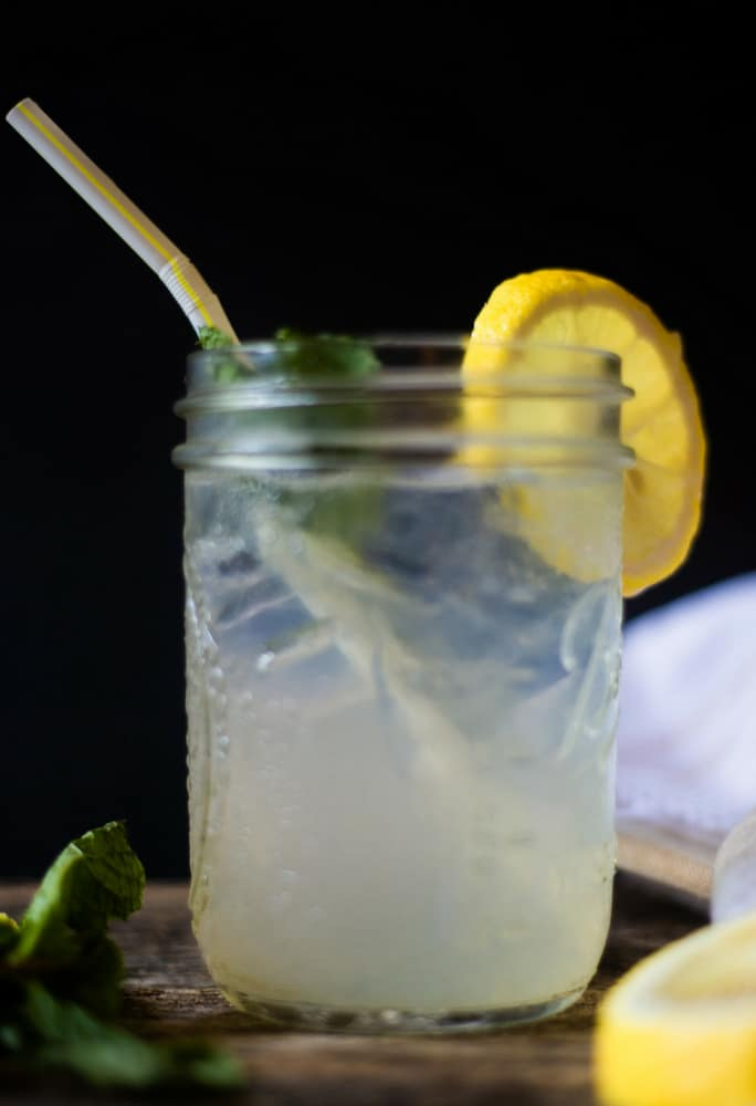 A refreshing mason jar of homemade mint ginger lemonade filled with ice and a yellow and white straw on a wooden table scattered with lemon and mint.