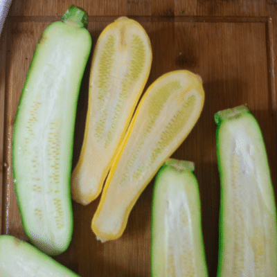 Zucchini has been sliced on a cutting board in half to make vegetable lasagna stuffed zucchini