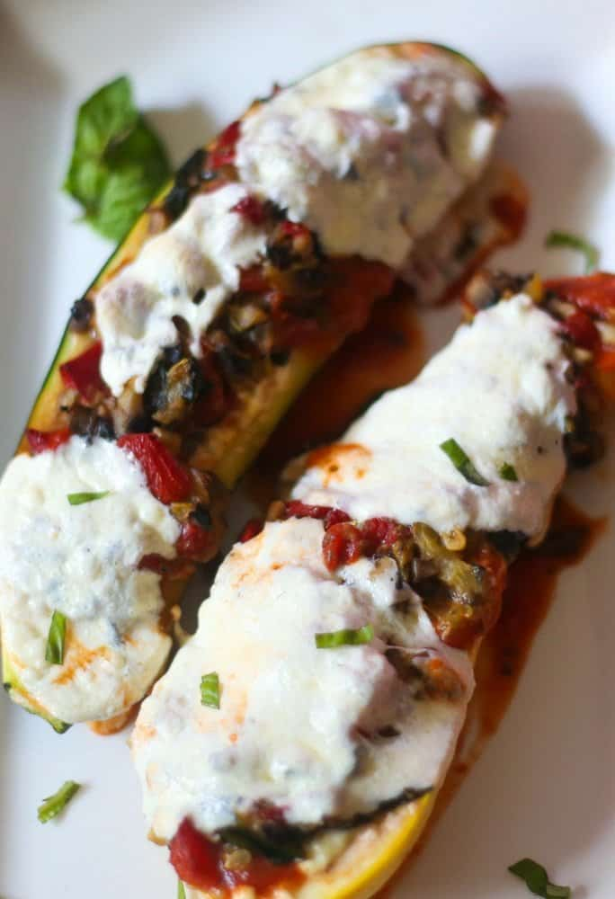 Vegetable lasagna stuffed zucchini boats on a white plate that has been roasted and topped with fresh mozzarella that has melted in the veggies and zucchini boat.