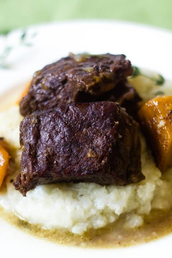 Fall off the bone tender Instant Pot Beer Braised short ribs over mashed cauliflower