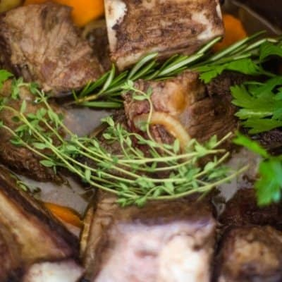 An instant pot filled with beef short ribs with carrots, onions, garlic, Guinness beer, beef stock, garlic, and herbs that will be quickly cooked to make beer braised beef short ribs
