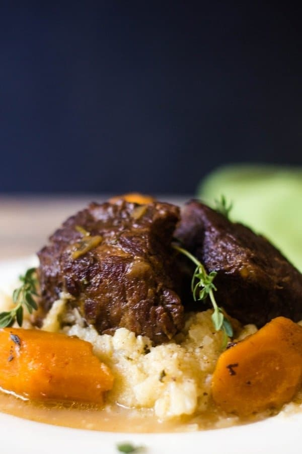 Deliciously glazed Beer Braised Short Ribs and carrots topping mashed cauliflower