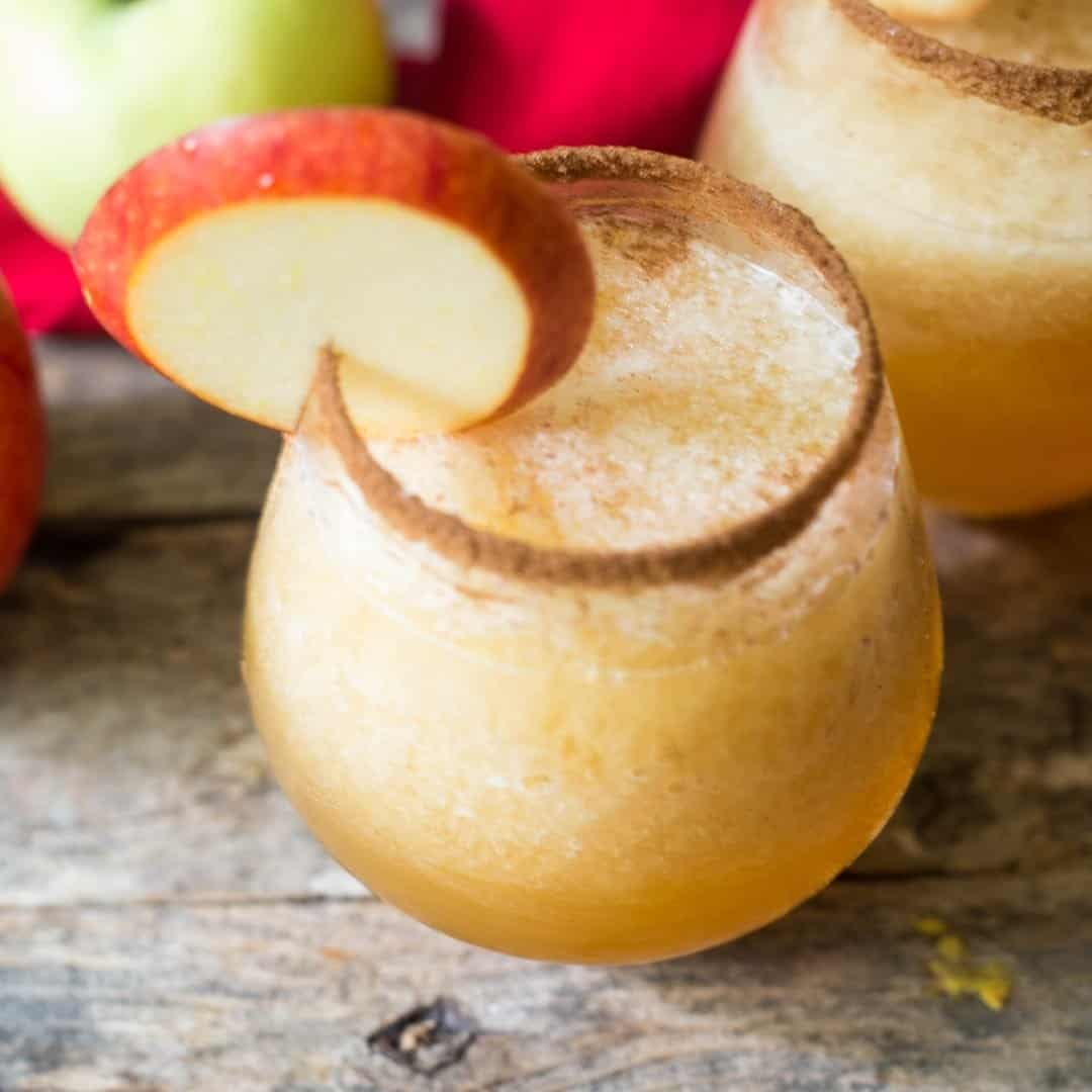 Caramel apple vodka slush cocktail with the glass rimmed in cinnamon sugar and a red apple wedge as a garnish