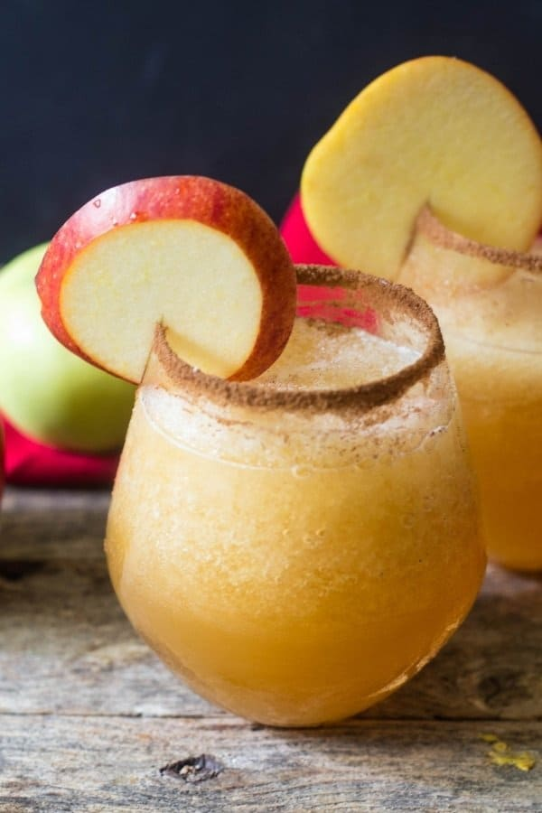 Caramel apple vodka smoothie in a clear glass with cinnamon sugar around the rim of the glass and an apple wedge in the rim of glass for garnish.