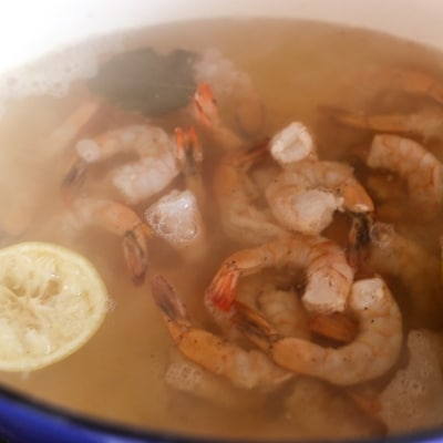 Fresh shrimp in poaching liquid in a large Dutch oven to make amazing poached shrimp