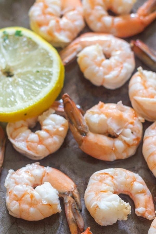 Juicy fresh shrimp that has been poached and sprinkled with lemon on a large tray.