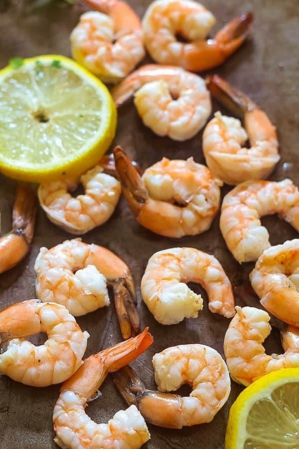 Fresh poached shrimp on a large platter with lemon slices scattered over the platter.
