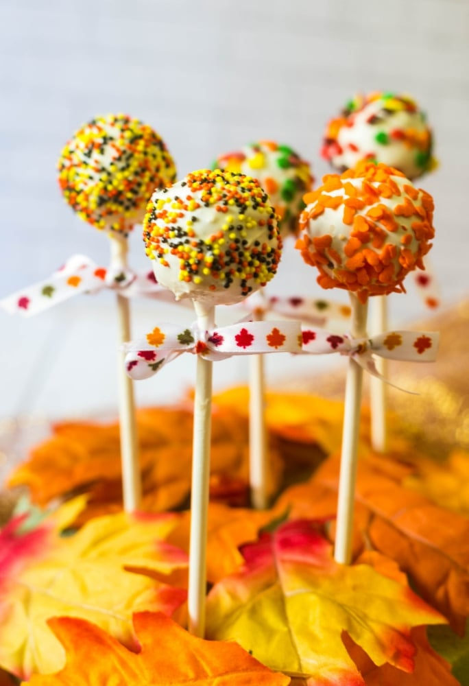 autumn cake pops decorated with fall leaves and pumpkins with bows on the pop sticks